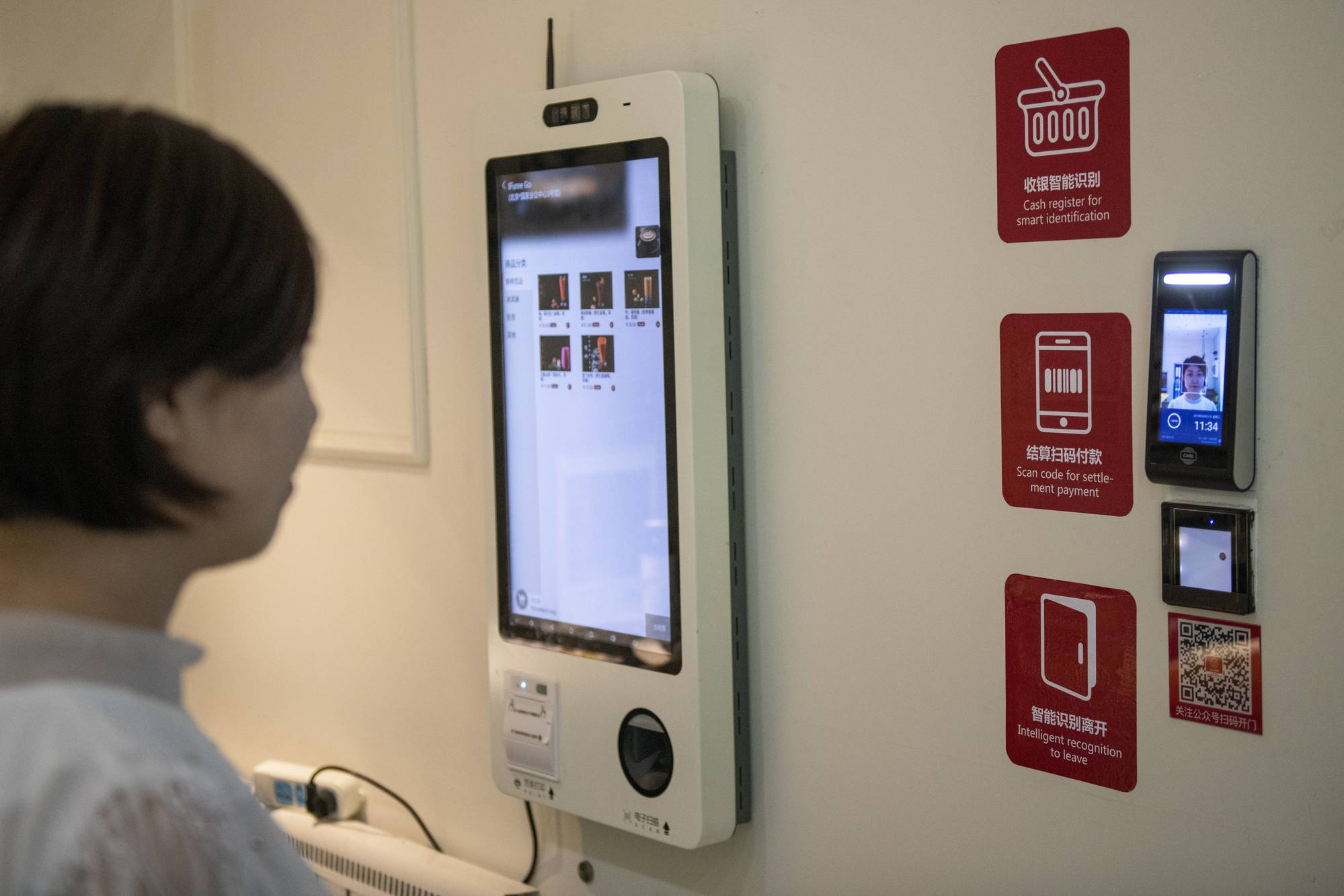 In this picture taken on August 21, 2019 a woman uses a facial recognition device installed at an IFuree Go self-service supermarket in Tianjin. - China's mobile payment infrastructure is already among the most advanced in the world, but facial payment technology is bidding to make QR phone codes old-fashioned. The newest payment systems being rolled out across the country only require a person's face to make purchases -- no mobile, no cash, no wallet. (Photo by Nicolas ASFOURI / AFP) / To go with AFP story China-technology-retail, FEATURE by Helen Roxburgh